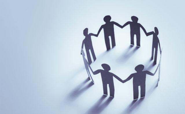 Grupa osób tworzy krąg symbolizujący wspólne działanie