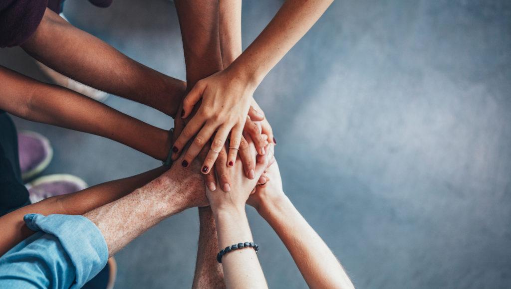 Zdjęcie. Ręce kilku osób położone jedne na drugich.