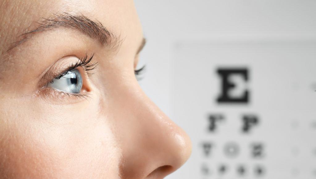 Kobieta patrzy w dal w tle tablica do badania ostrości widzenia