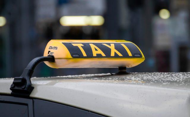 Zdjęcie. Na dachu samochodu przymocowany żółto-czarny szyld z napisem TAXI.