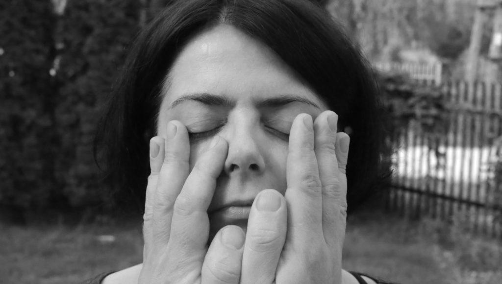 Czarno-białe zdjęcie. Kobieta ma zamknięte oczy. Na jej twarzy leżą ręce innej osoby.