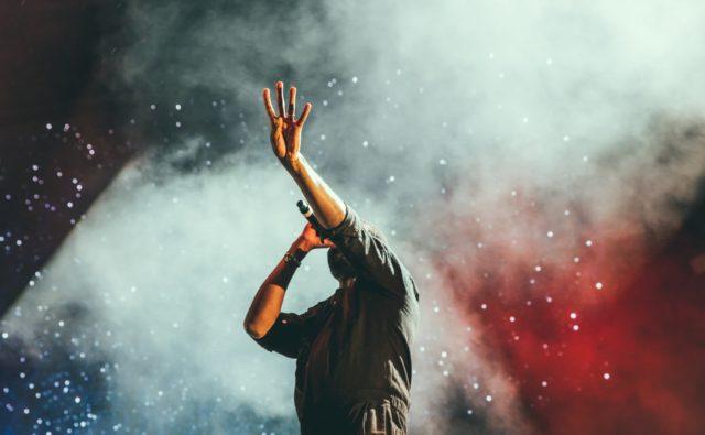Zdjęcie. Piosenkarz na scenie. Jedną rękę ma wysoko wzniesioną do góry. Palcami pokazuje cyfrę cztery.