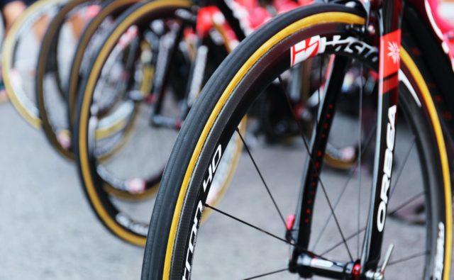 Zdjęcie. Kilka rowerów stoi obok siebie. Zbliżenie na przednie koła od rowerów.