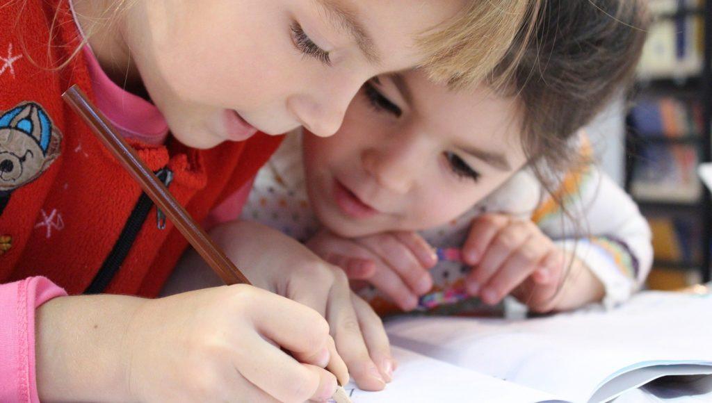 Zdjęcie. Jedna dziewczynka pisze ołówkiem w zeszycie, druga się temu przypatruje. Obie są pochylone nad kartką.