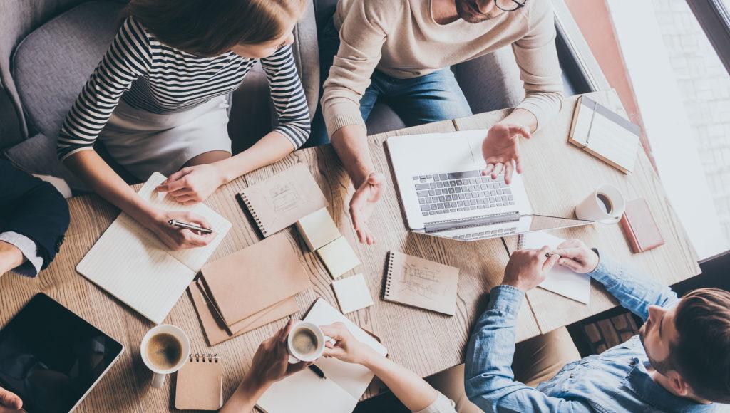 Zdjęcie. Kilkuosobowy zespół w trakcie zebrania. Na stole porozrzucane są notatki.
