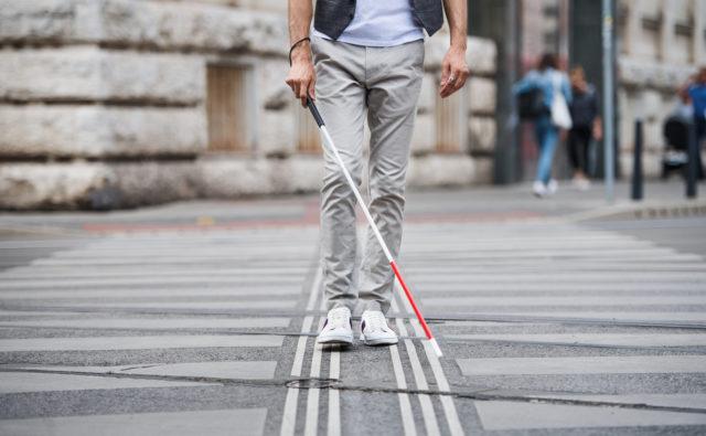 Mężczyzna idzie po ulicy z białą laską