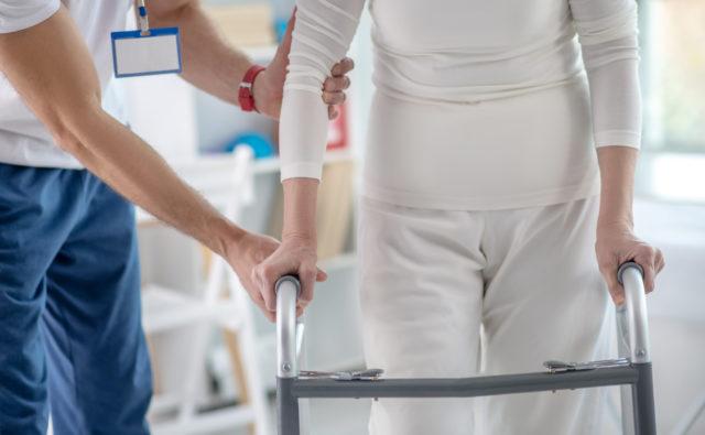 Pacjentka chodzi używając chodzika a asystuje jej rehabilitant