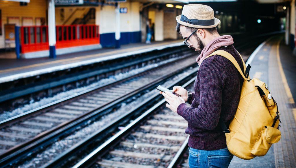 Mężczyzna stoi na peronie. Ma na głowie kapelusz, a na plecach żółty plecak. Mężczyzna sprawdza coś w telefonie.