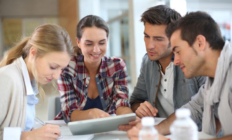Grupa młodych ludzi siedzi przy stole i omawia jakiś problem