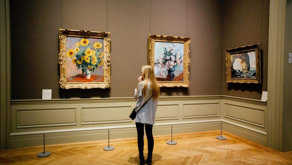 Kobieta w muzeum podziwia sztukę