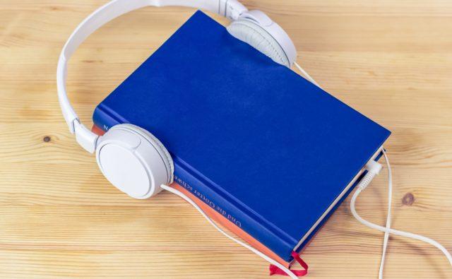 książka na stole, do której podłączone są słuchawki
