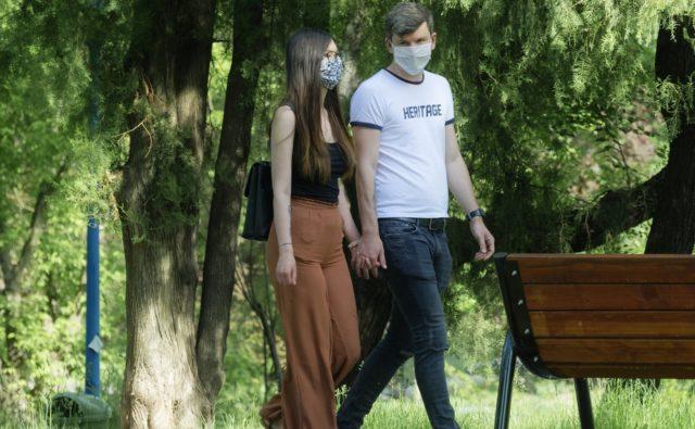 Mężczyzna i kobieta spacerują po parku, trzymając się za ręce. Oboje mają na twarzach maseczki ochronne.