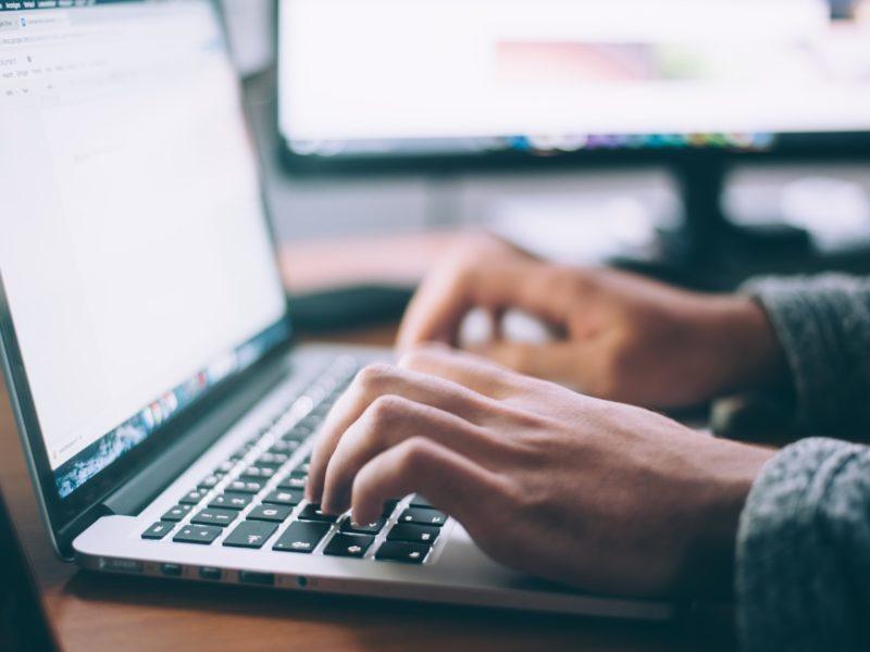 Osoba pisze przy użyciu klawiatury na laptopie.