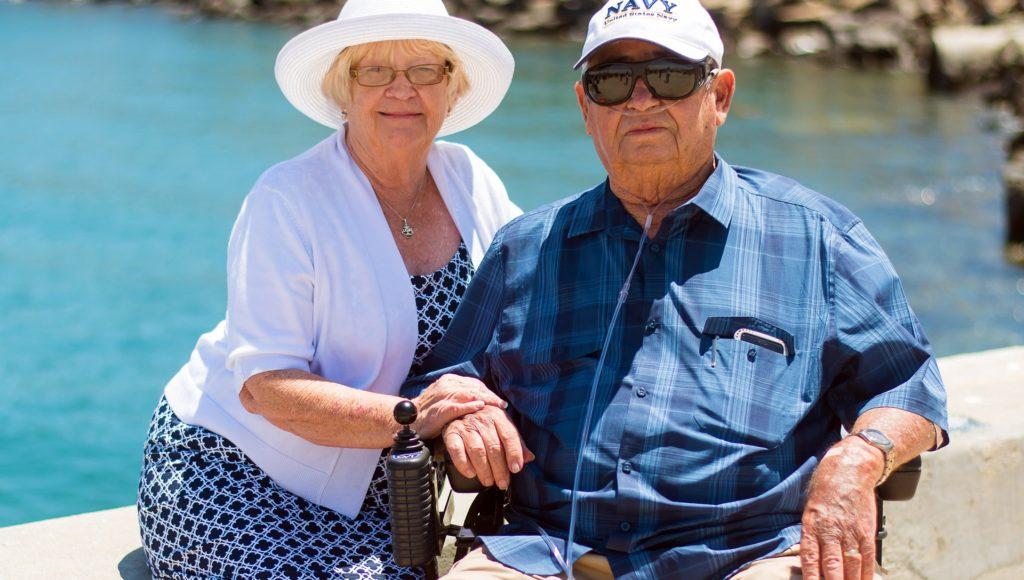 Starsza pani i starszy pan uśmiechają się, siedząc na ławce.