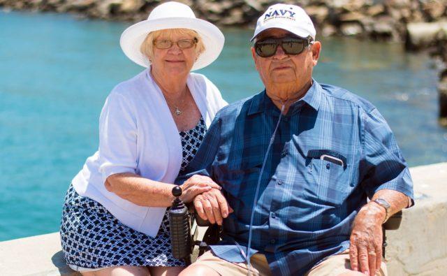 Starsza pani i pan uśmiechają się siedząc na ławce