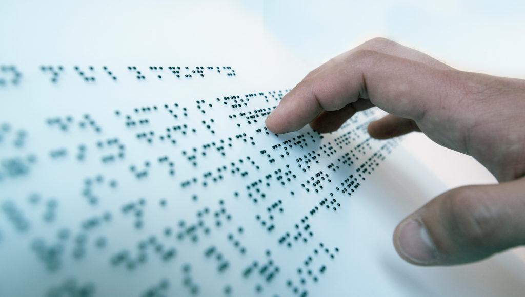 Palce osoby niewidomej wodzące po oznakowaniu w braju