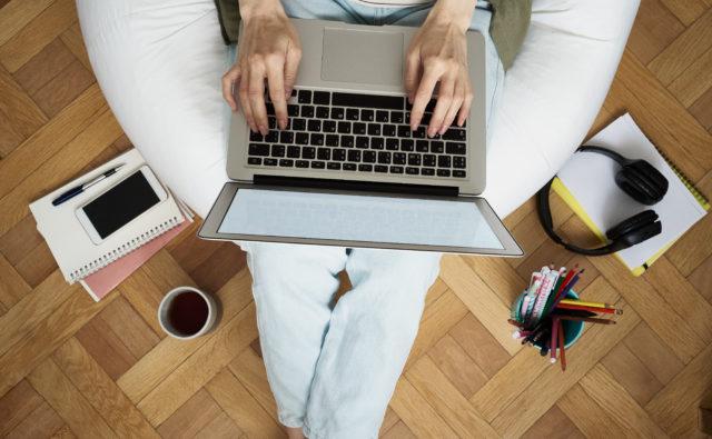 Osoba trzyma laptop na kolanach i coś pisze