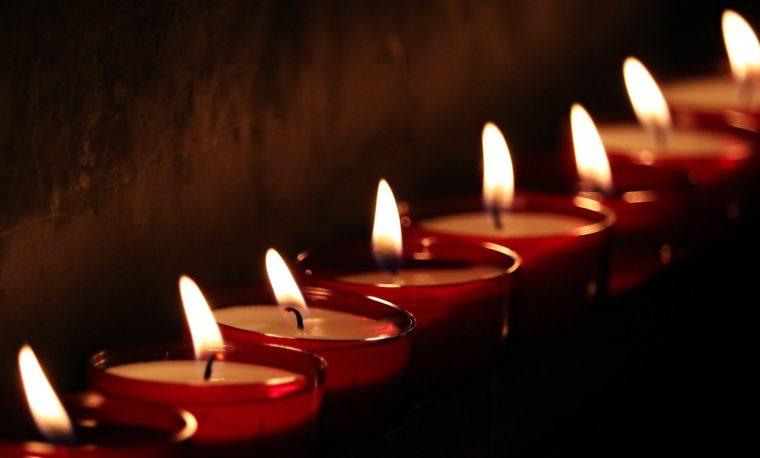 rząd zapalonych świeczek na ciemnym tle