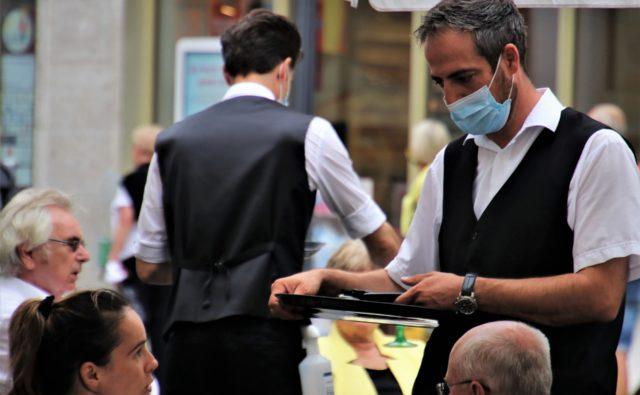kelner w maseczce obsługuje mężczyznę i kobietę siedzących przy stoliku