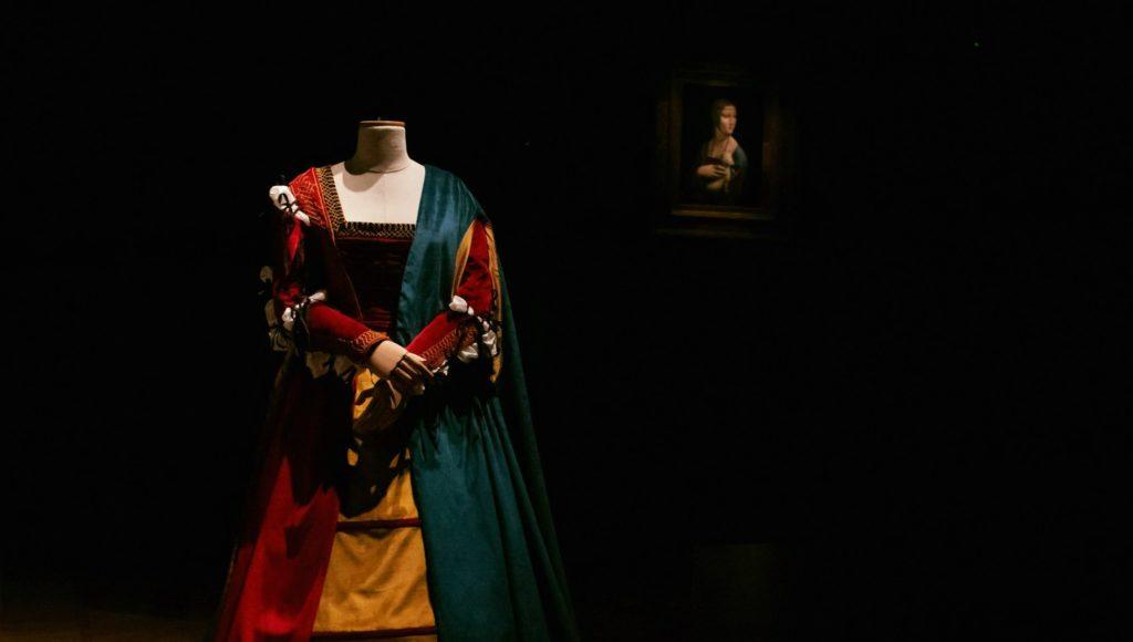 """zdjęcie sukni na czarnym tle, w oddali widać obraz """"Dama z gronostajem"""""""