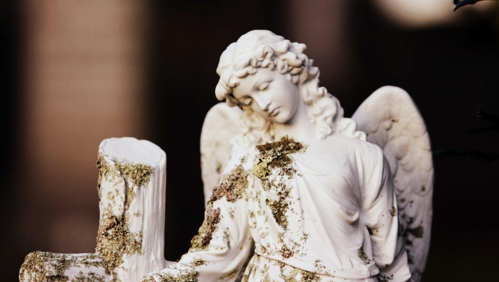 Aniołek nagrobny pochyla głowę nad zmarłymi
