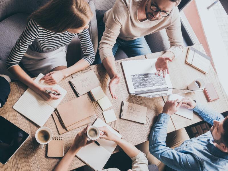 Grupa ludzi prowadzi dyskusję podczas spotkania. Wszyscy siedzą przy biurku zastawionym kawą i notatkami.