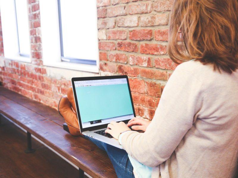kobieta siedzi na ławce wewnątrz pomieszczenia z murowanymi ścianami, położyła na ławce wyprostowane nogi, na kolanach trzyma laptopa; widzimy ją od tyłu
