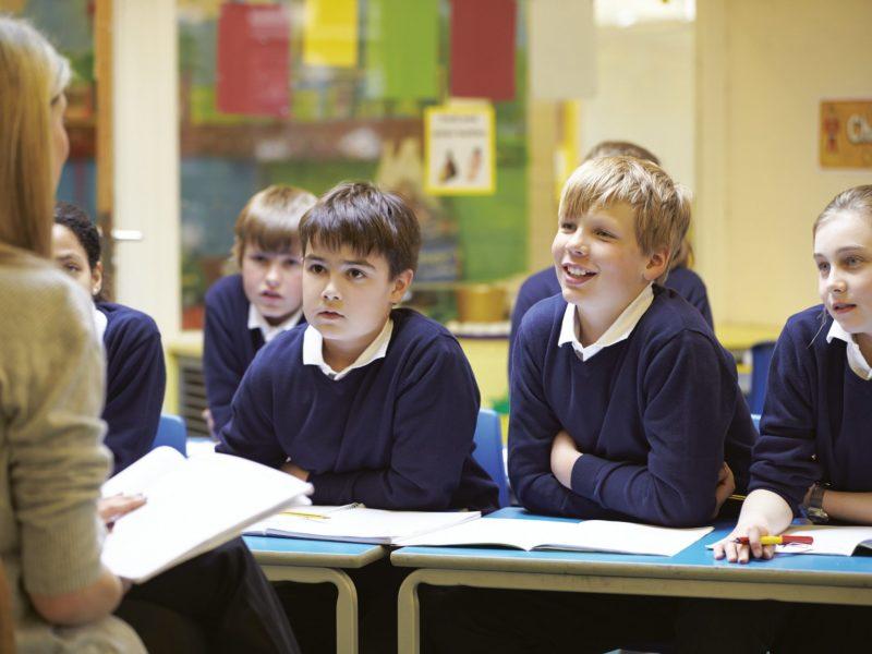 nauczycielka siedzi przed grupą uczniów i czyta im książkę. Dzieci uważnie słuchają, nauczycielkę widzimy od tyłu.