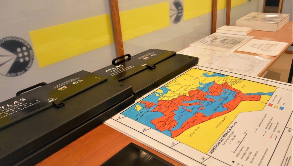 Atlasy i mapy ułożone na blacie
