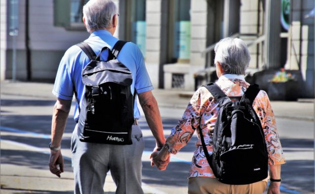 Dwoje seniorów - kobieta i mężczyzna - podczas spaceru. Trzymają się za ręce.