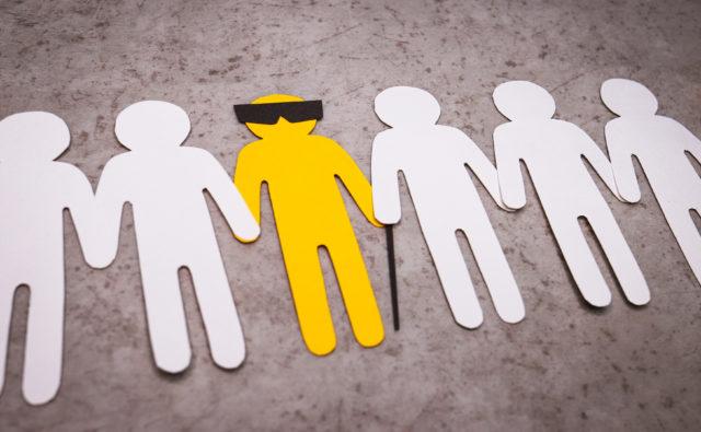 ludziki wycięte z papieru, trzymają się za ręce, wśród nich żółty ludzik z okularami i laską