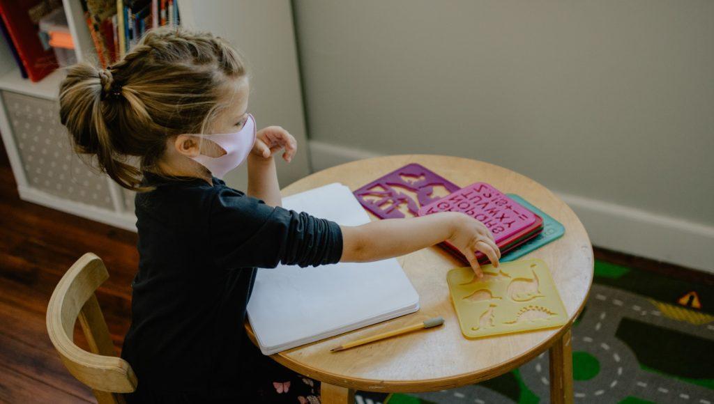 dziewczynka siedzi w klasie przy stoliku, ma na nim rozłożone zeszyty i pomoce szkolne; ma na twarzy maseczkę ochronną