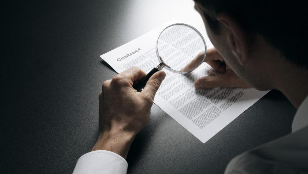 Mężczyzna czyta tekst na kartce za pomocą lupy.
