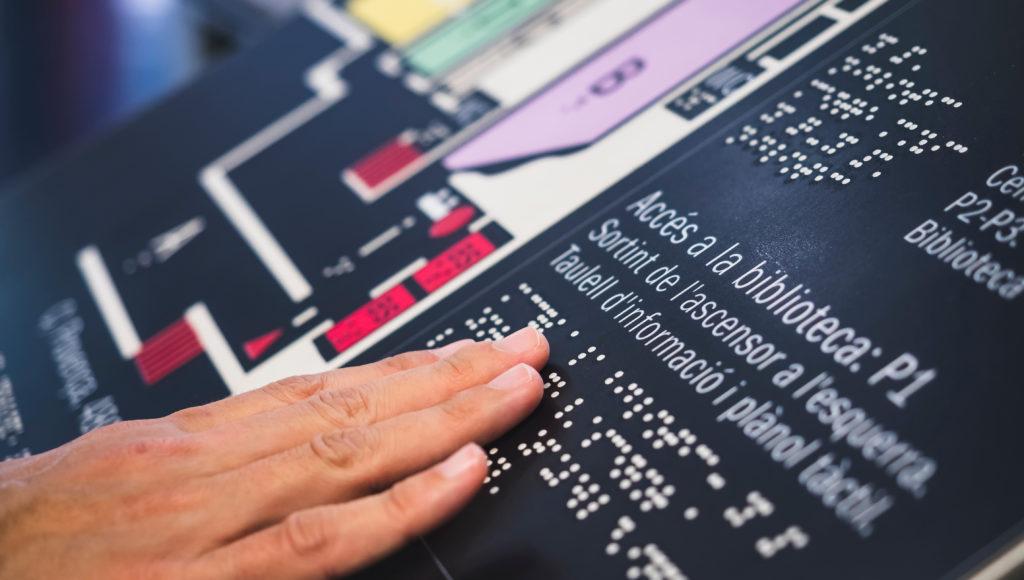 zbliżenie na dotykowy plan jakiegoś obiektu, do tego są napisy alfabetem brajla, widać tylko dłoń, która dotyka napisów