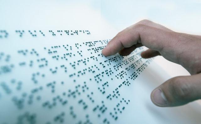 Ręka dotyka napisu w brajlu