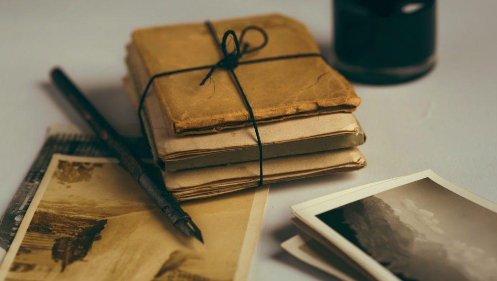 Archiwalne książki i fotografie leżą na stole