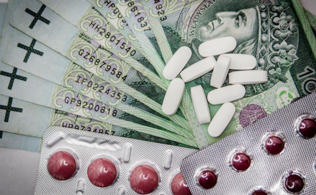 na zdjęciu widać pieniądze i leżące na nich tabletki i opakowania leków