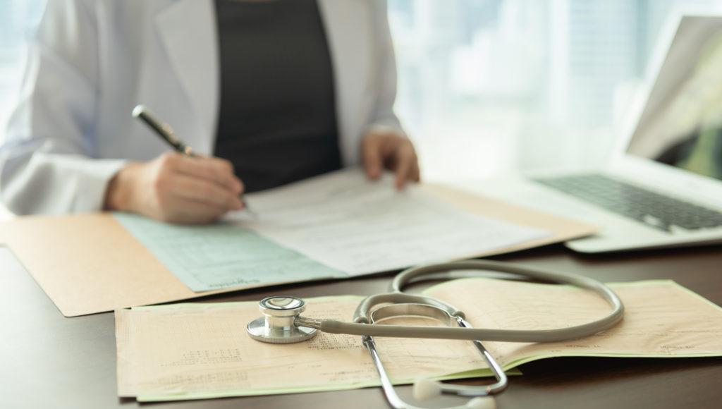 Lekarka wpisuje dane w kartę pacjenta
