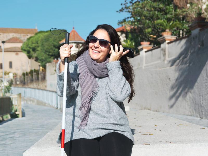 Uśmiechnięta kobieta siedzi na murku. W jednej ręce trzyma białą laskę, w drugiej, tuż przy uchu, smartfon.