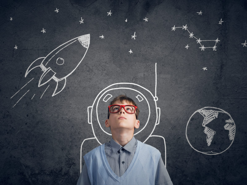 Grafika, na której znajduje się młody chłopak. Rozmyśla, spoglądając w górę. Wokół niego krążą rysunki przedstawiające zarys rakiety i ziemi. Wokół chłopaka obrysowany jest strój astronauty.