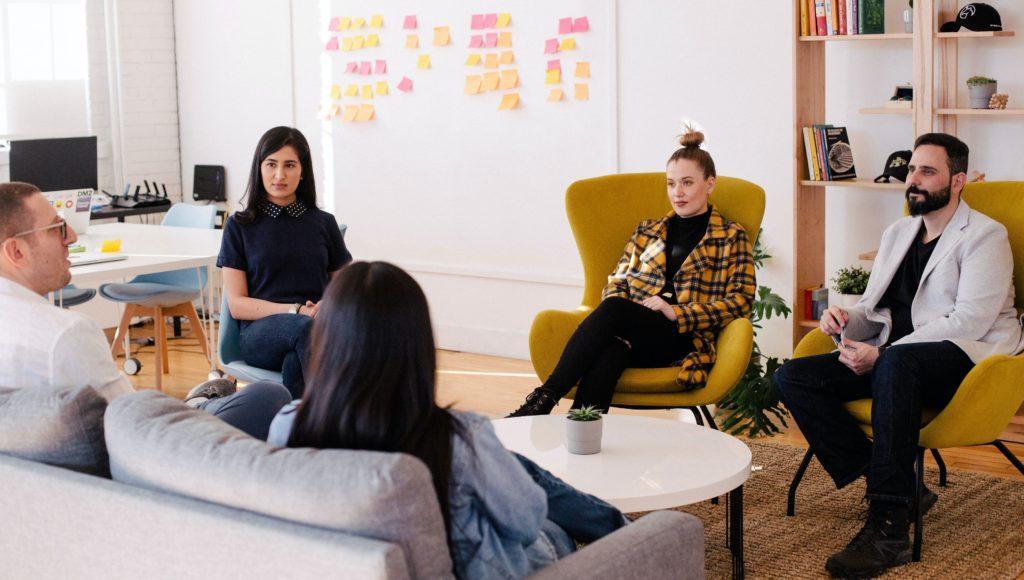 Młode osoby siedzą w pokoju i dyskutują