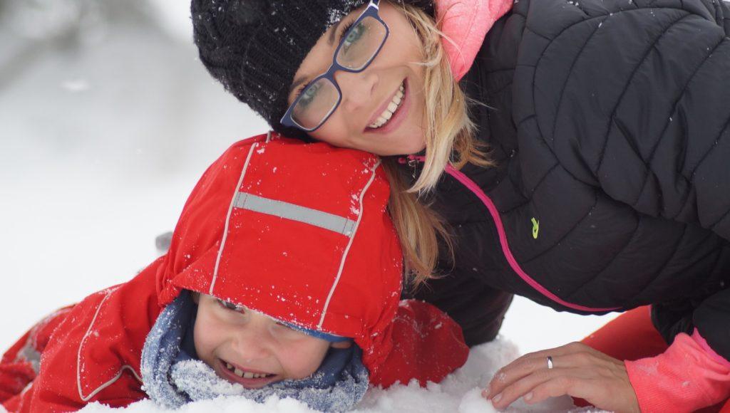 Kobieta w okularach bawiąca się z dzieckiem na śniegu.