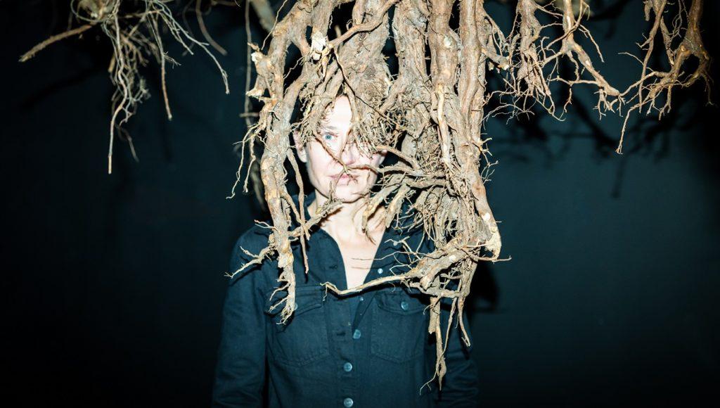 autorka wystawy, Joanna Rajkowska, stoi i patrzy na odbiorcę poprzez korzenie drzew, które zwieszają się z góry; widzimy tylko jej górną połowę ciała, jest silnie oświetlona białym światłem
