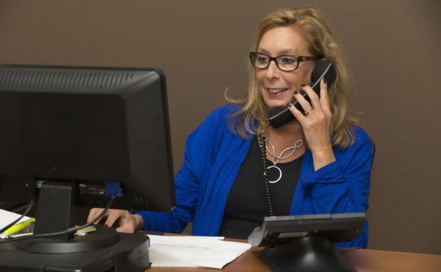 kobieta siedzi za biurkiem, patrzy na monitor komputera i rozmawia przez telefon stacjonarny