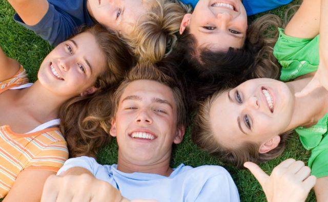 Dzieci w kręgu leżą na trawie i robią sobie zdjęcie