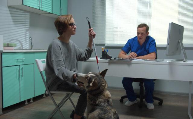 Osoba niewidoma z psem przewodnikiem w gabinecie lekarza rehabilitanta