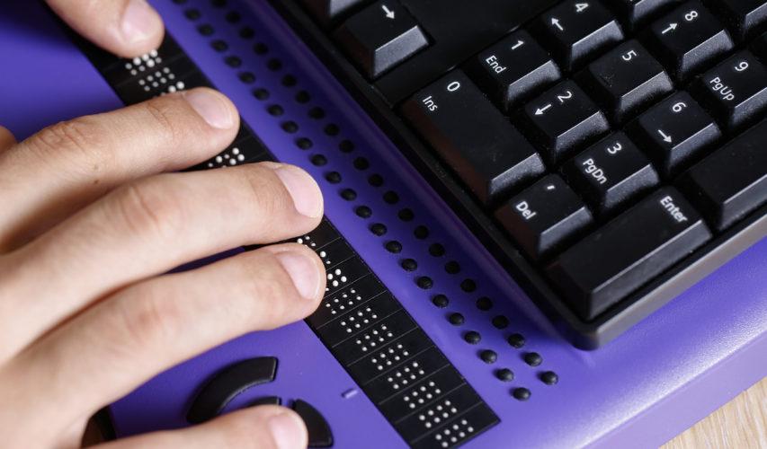 Widok na palce obsługujące notatnik brajlowski
