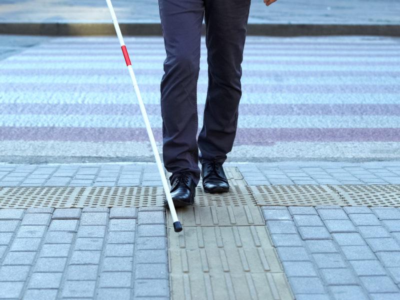 Niewidoma mężczyzna idzie z białą laską po ścieżce dotykowej