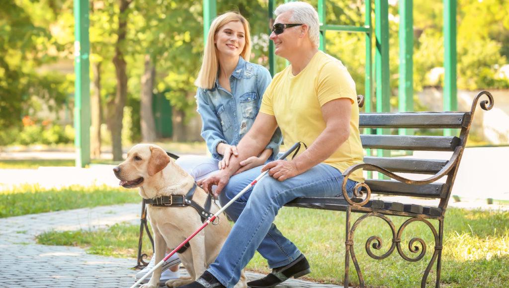 Mężczyzna niewidomy siedzi na ławce z kobietą w parku
