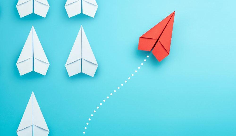 Białe statki na niebieskim tle, jeden - czerwony - odpływa od tych białych w prawą stronę